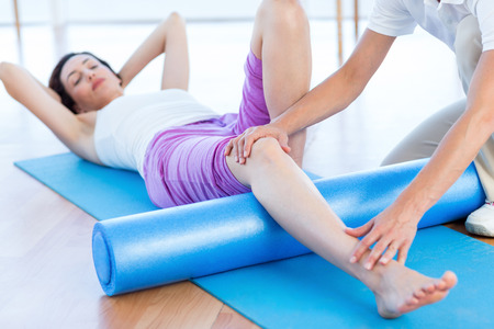 knees: Trainer working with woman on exercise mat in medical office
