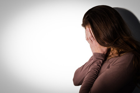 apprehensive: Depressed woman with head in hands on white background Stock Photo