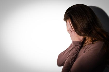 desolaci�n: Mujer deprimida con la cabeza en las manos sobre fondo blanco
