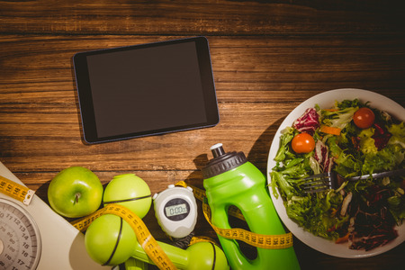 Tablet with indicators of healthy lifestyle on wooden table photo