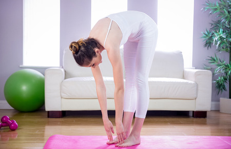 touching toes: Fit woman doing yoga on mat at home in the living room