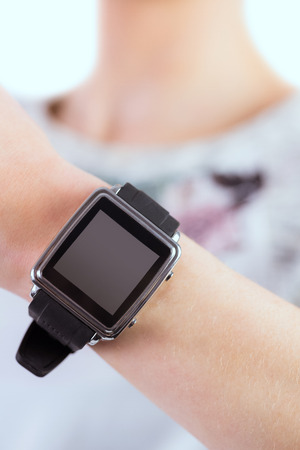 portable information device: Woman wearing her smartwatch on white background Stock Photo
