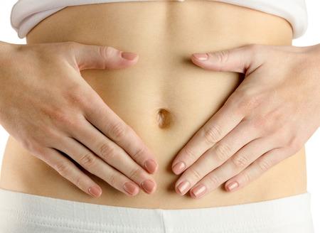 silhouette femme: Slim femme de toucher son ventre sur fond blanc