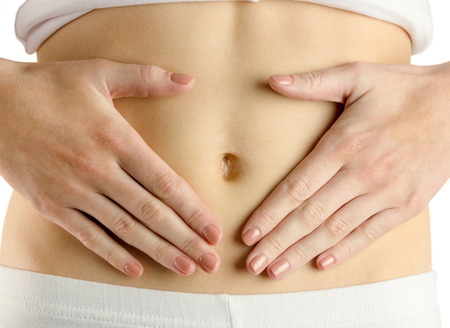 body concern: Slim woman touching her belly on white background