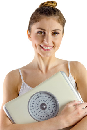 body concern: Slim woman holding weighing scales on white background