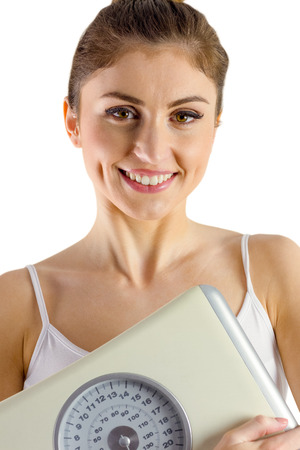 weighing scales: Slim woman holding weighing scales on white background