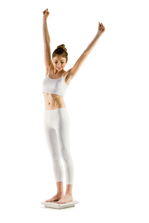 euphoria: Slim woman cheering on scales on white background