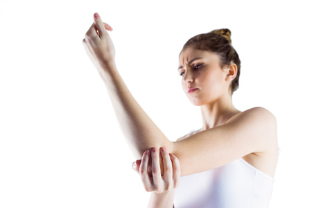 wincing: Fit woman with elbow injury on white background