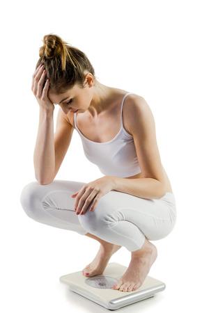 mujer decepcionada: Mujer delgada decepcionado en las escalas en el fondo blanco