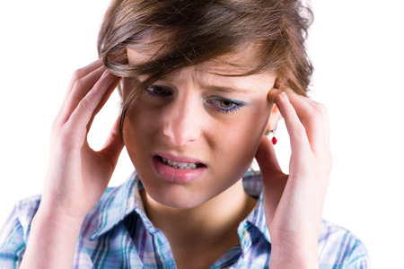 wincing: Pretty brunette getting a headache with hands on head on white background Stock Photo