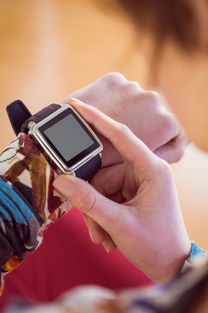 leisure wear: Fit woman using her smartwatch on brown background Stock Photo