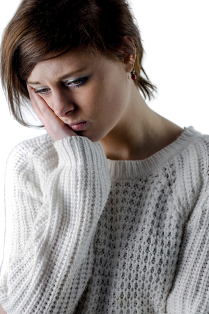 unhappiness: Pretty brunette feeling sad on white background Stock Photo