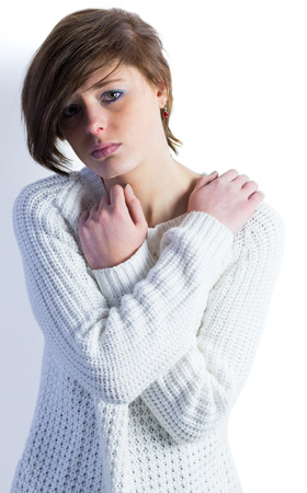 wistfulness: Sad pretty brunette looking at camera with arms crossed on white background