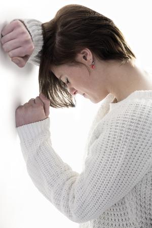desolaci�n: Triste guapa morena apoy�ndose contra la pared en el fondo blanco