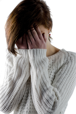 bleakness: Sad pretty brunette crying with head on hands on white background