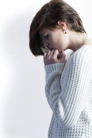 desolaci�n: Triste guapa morena sosteniendo su cabeza en el fondo blanco