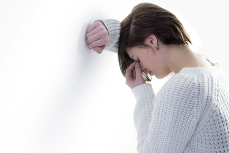 unhappiness: Sad pretty brunette leaning against wall on white background
