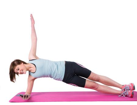 body toning: Pretty brunette doing side plank on exercise mat on white background Stock Photo
