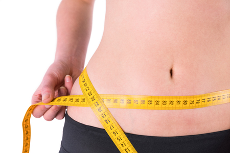 silhouette feminine: slim woman measuring waist with tape measure on white background