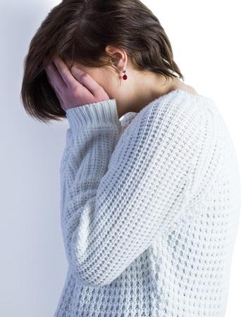 desolaci�n: Triste guapa morena llorando con la cabeza en las manos sobre fondo blanco Foto de archivo