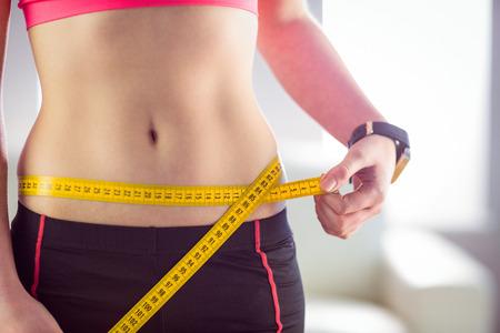 cintura: Mujer delgada que mide la cintura con cinta métrica en casa en la sala de estar