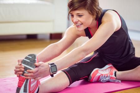 ejercicio: Ajustar la mujer estira en la estera de ejercicio en casa, en la sala de estar