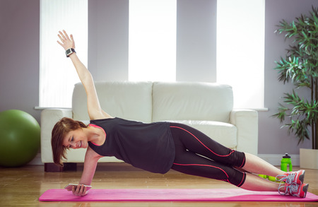 body toning: Fit woman doing side plank at home in the living-room Stock Photo