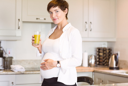 mature adult: Pregnant woman having a glass of orange juice at home in the kitchen Stock Photo