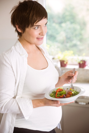 mature adult: Pregnant woman having bowl of salad at home in the kitchen