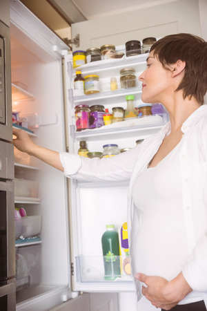 mature adult: Pregnant woman opening the fridge at home in the kitchen Stock Photo