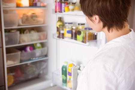 妊娠中の女性が台所で自宅の冷蔵庫を開く