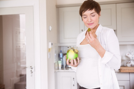 cravings: Pregnant woman eating jar of pickles at home in the kitchen Stock Photo