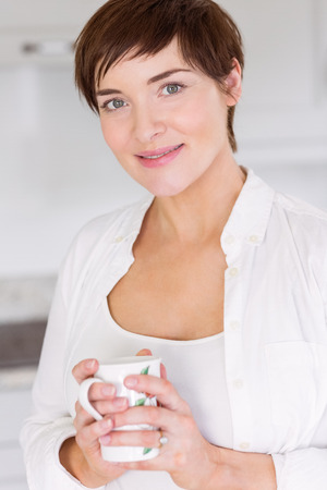 mature adult: Pregnant woman having a hot drink at home in the kitchen Stock Photo