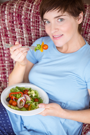 mature adult: Pregnant woman eating a salad at home in the living room