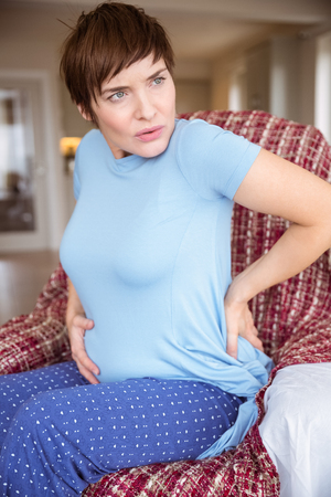 contraction: Pregnant woman getting a contraction at home in the living room