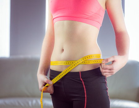 woman measuring waist: Slim woman measuring waist with tape measure at home in the living-room Stock Photo