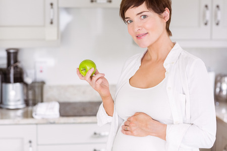mature adult: Pregnant woman eating an apple at home in the kitchen
