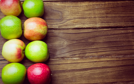 Fresh colorful apples on wooden background photo