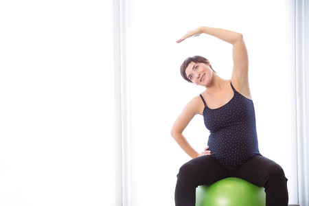 home keeping: Pregnant woman keeping in shape at home