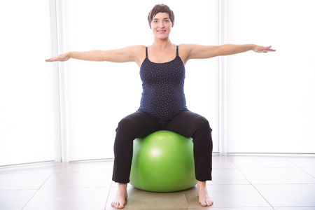 mature adult: Pregnant woman keeping in shape at home