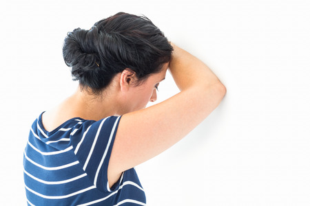 tied hair: Sad woman leaning against the wall on white background Stock Photo
