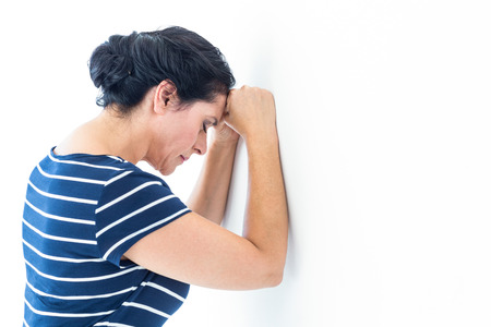 pessimistic: Sad woman leaning against the wall on white background Stock Photo