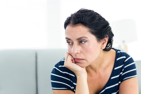 pessimistic: Unhappy woman sitting on the couch on white background Stock Photo