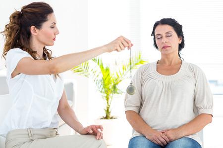 Therapist hypnotizing her patient on white background Zdjęcie Seryjne