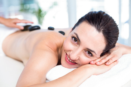 hot stone massage: Smiling brunette getting hot stone massage in a healthy spa