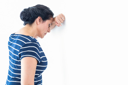 wistfulness: Sad woman leaning against the wall on white background Stock Photo