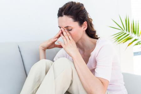 desolaci�n: Morena triste que se sienta en el sof� en el fondo blanco