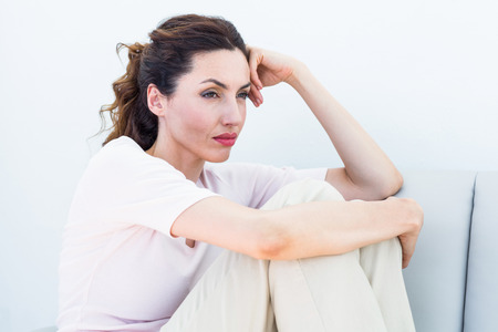 solitariness: Sad brunette sitting on the couch on white background