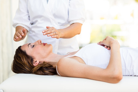 spa treatment: Calm woman receiving reiki treatment in the health spa Stock Photo