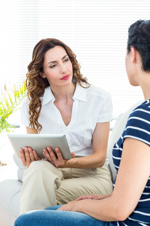 mental health: Therapist listening her patient and holding tablet on white background